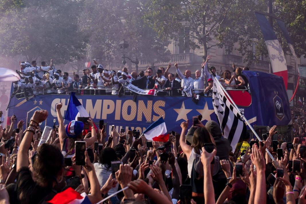 Le Bus des Bleus traverse les Champs-Elysée dans la foule